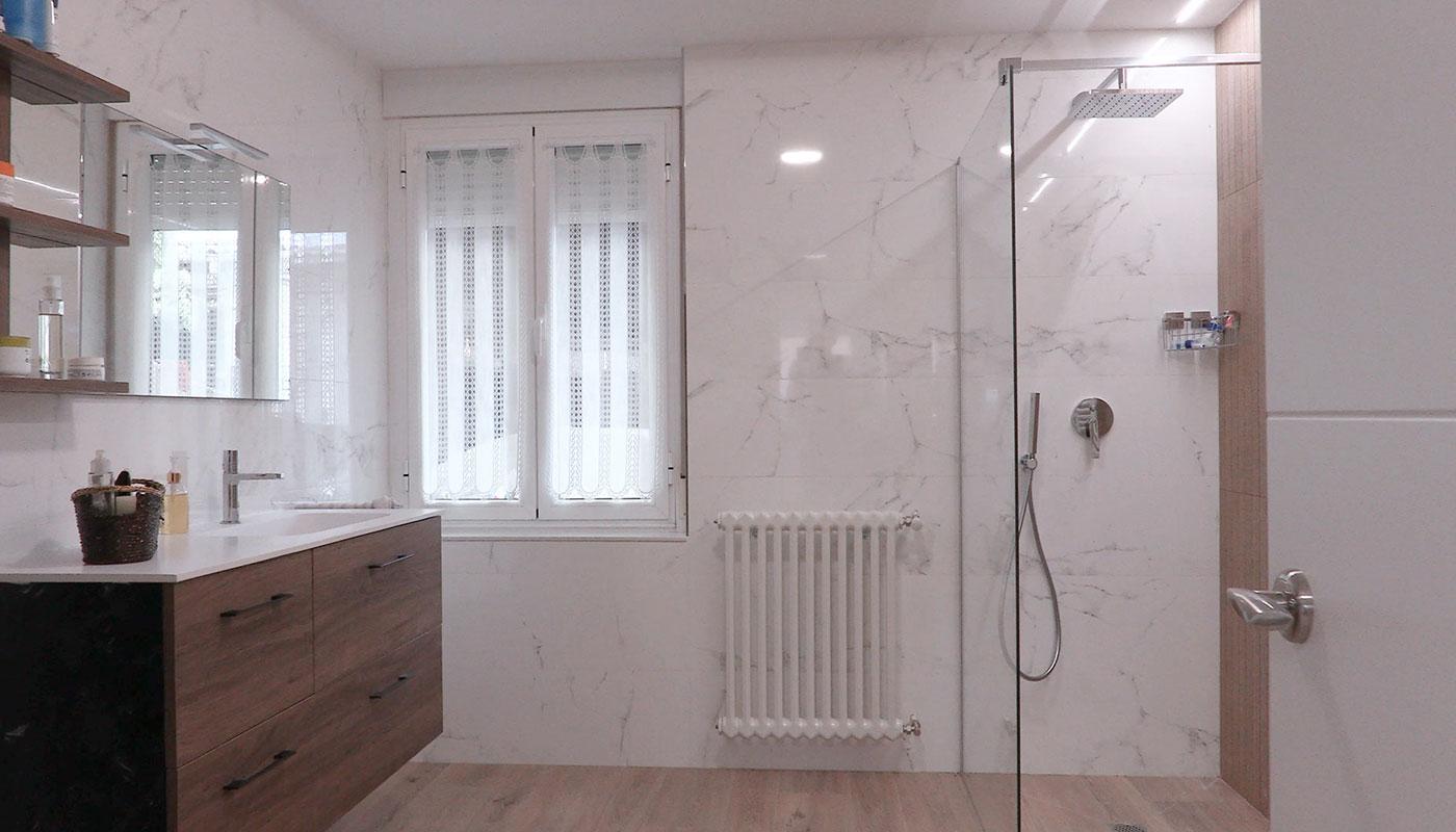 Reforma de baño con muebles en laminado nogal y revestimiento ducha en material porcelanico
