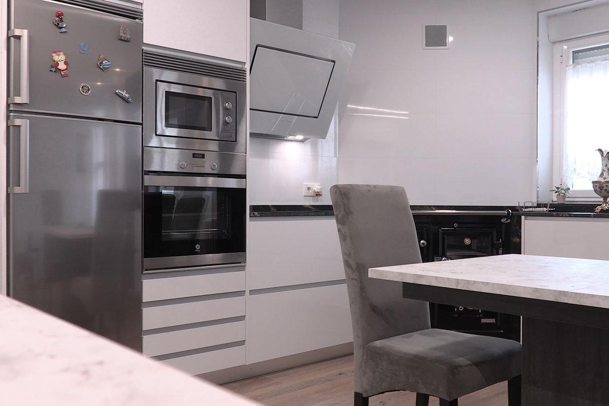 Cocina en blanco brillo con mesa central y cocina de leña