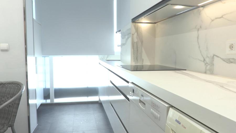 Vista de frente de cocina en blanco brillo con placa y campana