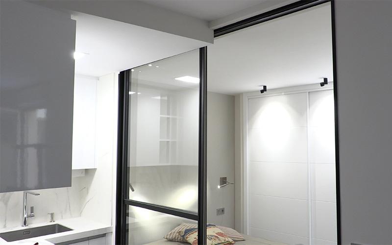 Puerta corredera en cristal con marco negro brillo para separar cocina y dormitorio en estudio pequeño en León
