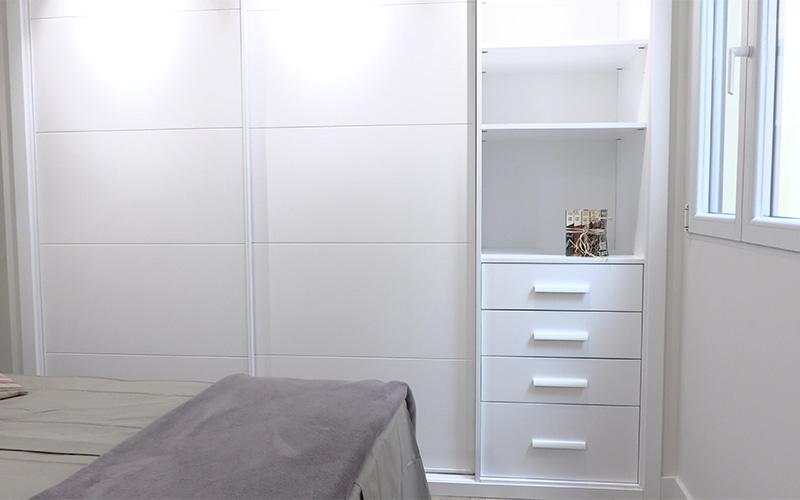 Vista de armario lacado blanco con dos puertas correderas, baldas y cajones en el lateral - Proyecto Reforma de estudio pequeño en León