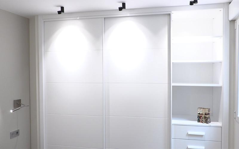 Vista de armario iluminado fabricado en lacado blanco con dos puertas correderas, baldas y cajones en el lateral - Proyecto Reforma de estudio pequeño en León