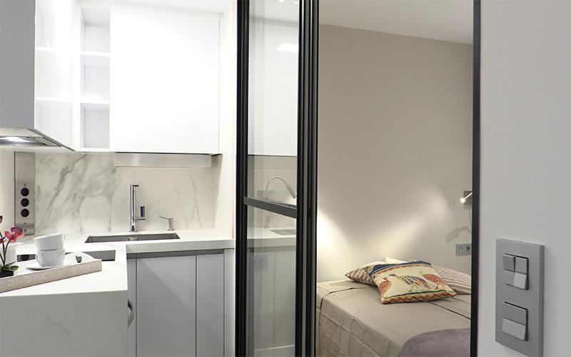 Cocina y dormitorio separados por puerta corredera en cristal y carpintería negro brillo - Proyecto Reforma de estudio pequeño