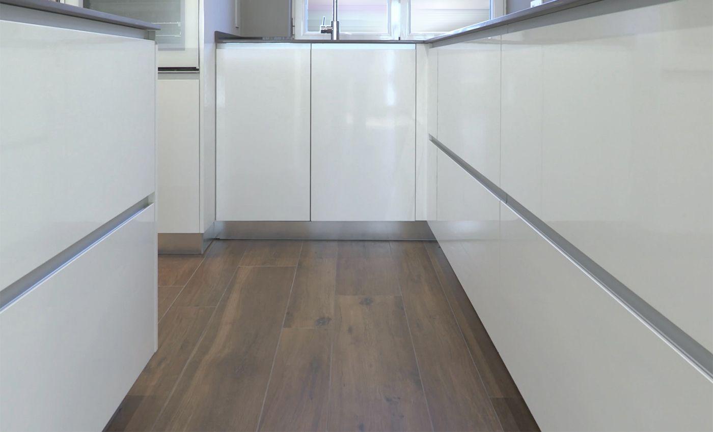 Detalle del suelo radiante material porcelánico y acabado nogal en reforma integral de piso