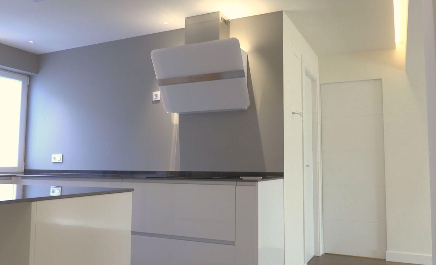 Vista de frente de cocina blanco brillo Senssia abierta al salón y con campana de pared decorativa
