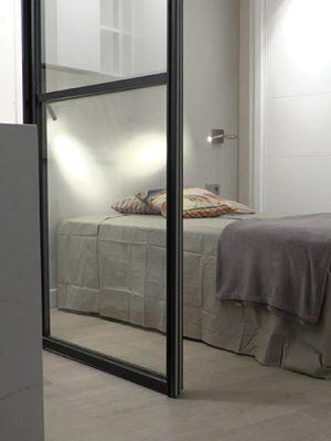 Detalle suelo, puerta corredera y cama en dormitorio - Proyecto Reforma de estudio pequeño en León