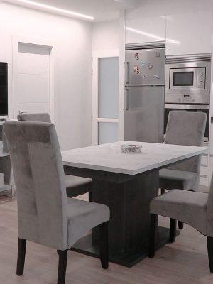 Reforma de cocina blanca con mesa central